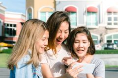 Group of young Asian Women selfie themselves with a phone in a pastel town after shopping. Young women group do outdoor activity under the blue sky. Outdoor Royalty Free Stock Photography
