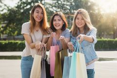 Group of young Asian woman shopping in an outdoor market with shopping bags in their hands. Group of young Asian women shopping in an outdoor market with Stock Images