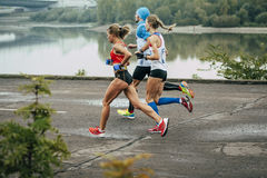 Group of young athletes running along embankment of river Royalty Free Stock Photography