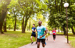 Group of young athletes running in green sunny park. Group of young athletes running in green sunny summer park Royalty Free Stock Photos