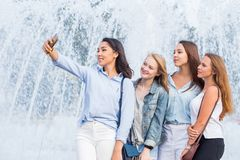 A group of young attractive girls of students takes a selfie on the background of a beautiful fountain royalty free stock photography