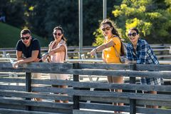 Group of young and attractive people is standing on bridge in park. stock photo