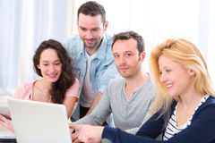 Group of 4 young attractive people working on a laptop Royalty Free Stock Photography