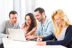 Group of 4 young attractive people working on a laptop Stock Photo