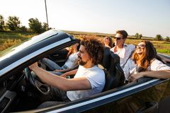 Group of young beautiful girls and guys in sunglasses smile and ride in a black cabriolet on the road on a sunny day. stock image