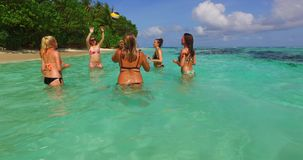 Group of young beautiful girls playing beach ball and sunbathing in aqua blue clear sea water and sky Stock Images
