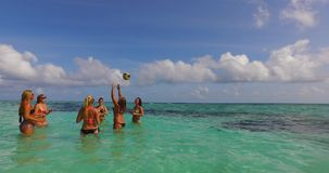 V12678 group of young beautiful girls playing beach ball and sunbathing in aqua blue clear sea water and sky. Group of young beautiful girls playing beach ball Royalty Free Stock Photo