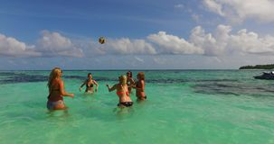V12690 group of young beautiful girls playing beach ball and sunbathing in aqua blue clear sea water and sky. Group of young beautiful girls playing beach ball Stock Photography