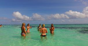 V12691 group of young beautiful girls playing beach ball and sunbathing in aqua blue clear sea water and sky. Group of young beautiful girls playing beach ball Royalty Free Stock Photos