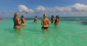 V12685 group of young beautiful girls playing beach ball and sunbathing in aqua blue clear sea water and sky. Group of young beautiful girls playing beach ball Stock Photo