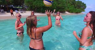 V12681 group of young beautiful girls playing beach ball and sunbathing in aqua blue clear sea water and sky. Group of young beautiful girls playing beach ball Royalty Free Stock Photos