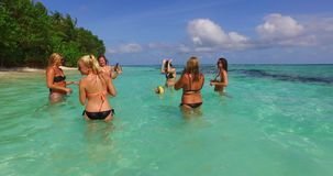 V12686 group of young beautiful girls playing beach ball and sunbathing in aqua blue clear sea water and sky. Group of young beautiful girls playing beach ball Stock Photo