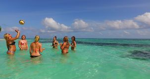 V12689 group of young beautiful girls playing beach ball and sunbathing in aqua blue clear sea water and sky. Group of young beautiful girls playing beach ball Stock Photography