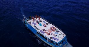 V09130 group young beautiful girls sunbathing on a boat with aerial view in clear aqua blue sea water and blue sky. Group young beautiful girls sunbathing on a Royalty Free Stock Photos