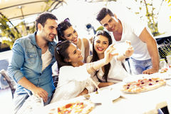 Group of young beautiful people sitting in a restaurant and taki Stock Photography