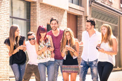 Group of young best friends having fun together walking in town. Group of young best friends having fun together walking on town street - Moment of technology Stock Image
