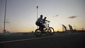 Group of young bikers friends hanging and riding on smoky bikes doing stunts and ollie tricks at the sunset in slow motion -. Group of young bikers friends stock video