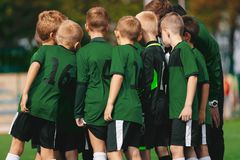 Group of Young Boys in Green Jersey Shirts Standing with Coach on Soccer Field. Sports Team Putting Their Hands in Together. Pre-game Coach Speech. Junior Kids royalty free stock images