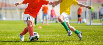 A group of young boys kicking football game on the sports field. Soccer school competition. Children footballers in yellow and red jersey shirts royalty free stock images