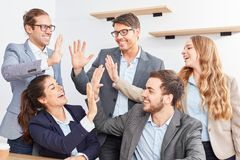 Group of young business people celebrates a success. Group of young business people gives themselves the high five and celebrates a success stock photography