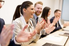 Young business people clapping their hands in office Royalty Free Stock Photo