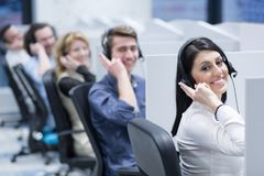 Call center operators. Group of young business people with headset working and giving support to customers in a call center office royalty free stock image