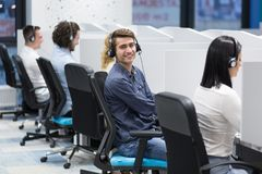 Call center operators. Group of young business people with headset working and giving support to customers in a call center office Stock Photo