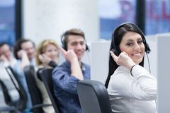 Call center operators. Group of young business people with headset working and giving support to customers in a call center office Royalty Free Stock Images