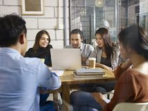 Group of young business people meeting in company. Group of five businesspeople entrepreneurs asian and caucasian men and women meeting in company office using Stock Photography