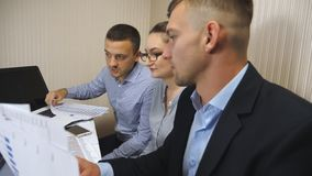 Group of young business people sitting at table in modern office and working on new project. Colleagues carefully look stock video footage