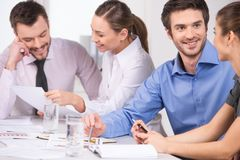 Group of young business people talking in couples. Royalty Free Stock Image
