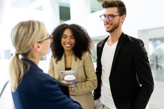 Group of young business people talking in a hallway of the company. Royalty Free Stock Photography