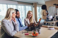 Young business people working together in creative office. Selective focus. Group of young business people working together in creative office. Selective focus royalty free stock image