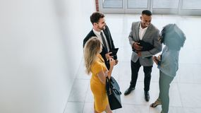 Corporate professionals having casual meeting in office lobby. Group of young business professionals standing together and having casual discussing in office royalty free stock images
