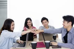Young business team joining hands after a meeting stock photography