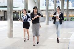 Group of young businesswoman at rush hour walking in the street and watch the clock checking time to late on city streets. Group of young business women at rush royalty free stock photo