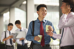 Group of young businessmen working and discussing outdoors, smiling, holding coffee Royalty Free Stock Photo