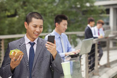 Group of young businessmen working outdoor and eating Royalty Free Stock Images