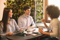 Group of young businesspeople having briefing in cafe royalty free stock photo