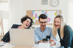 Group of young businesspeople with laptop working together in a modern office. royalty free stock image