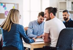 Group of young businesspeople sitting around table in a modern office, having meeting. Group of young, cheerful businesspeople sitting around table in a modern royalty free stock photos