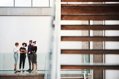 Group of young businesspeople standing near staircase, talking. royalty free stock photo