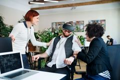 Group of young businesspeople with VR goggles in office, start-up concept. A group of young businesspeople with VR goggles talking in office, start-up concept stock photo