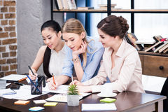 Group of young businesswomen working together at table with papers Royalty Free Stock Images