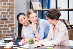 Group of young businesswomen working together at table with papers Royalty Free Stock Photos