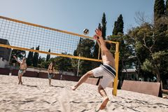 Group young caucasian friends playing volleyball on beach on summer vacation royalty free stock image