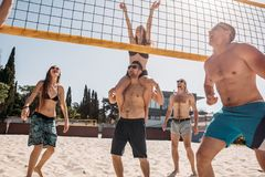 Group young caucasian friends playing volleyball on beach on summer vacation royalty free stock images