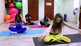 Group of young caucasian women meditating sitting after training in fitness studio stock video footage