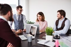 A group of young business people with laptop sitting in an office, talking. A group of young cheerful business people with laptop sitting in an office, talking royalty free stock image