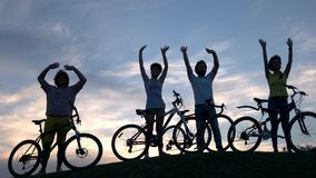 Group of young cheerful cyclists at sunset. stock video